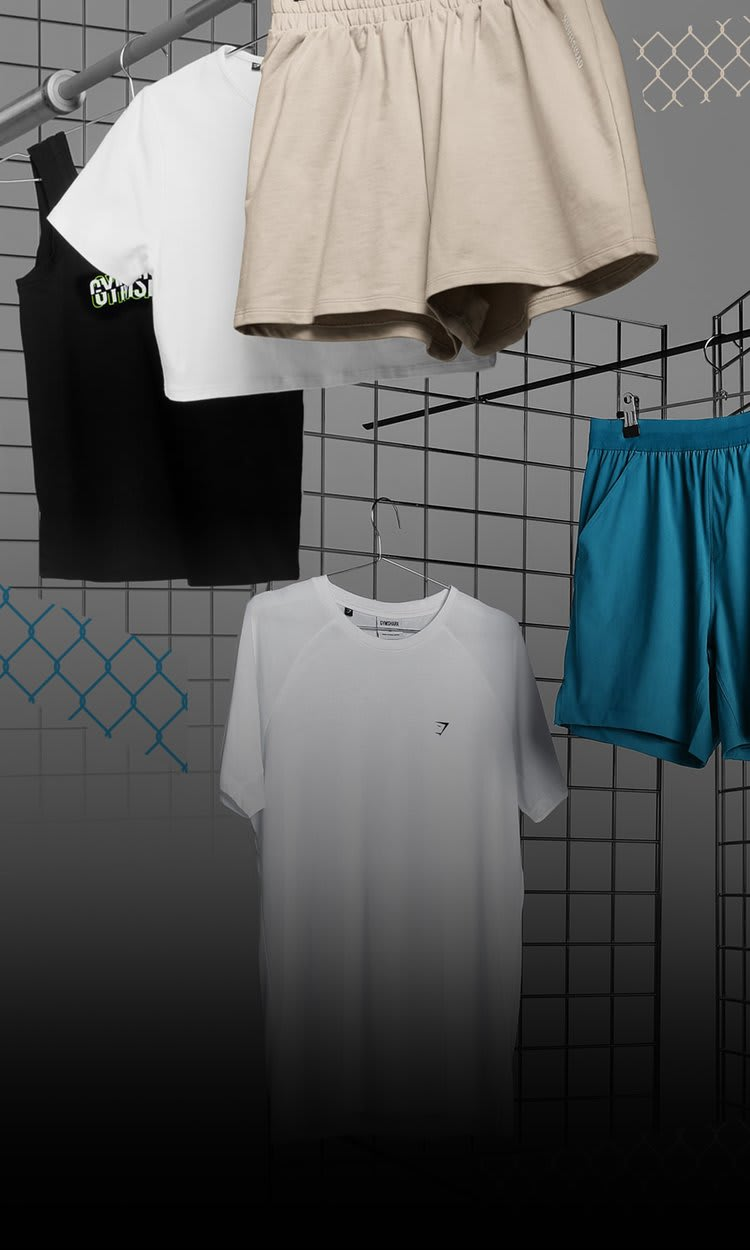 Womens Slice and Throw On Shorts hanging up on railings next to Mens Studio with a grey background.