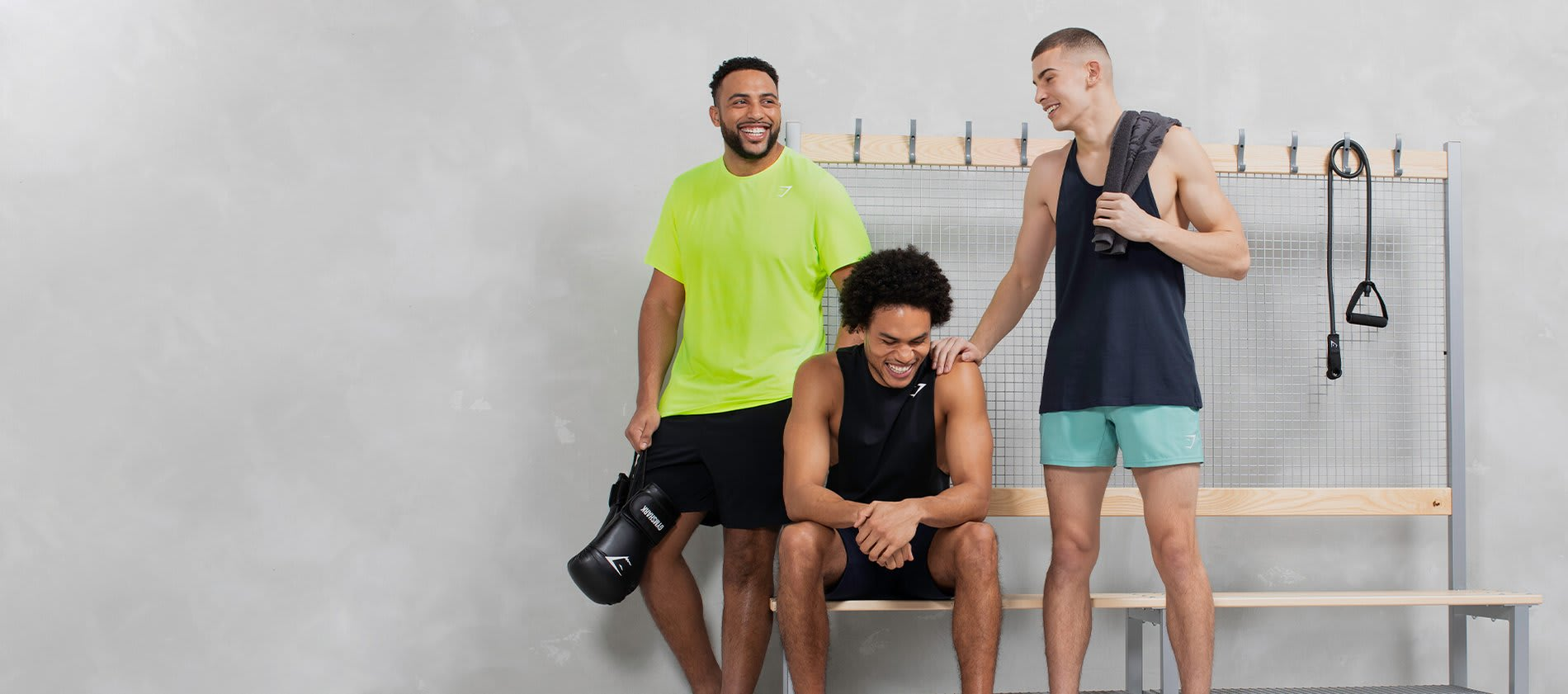 Three male models laughing together pose in a bright locker room wearing the Gymshark Essentials collection.