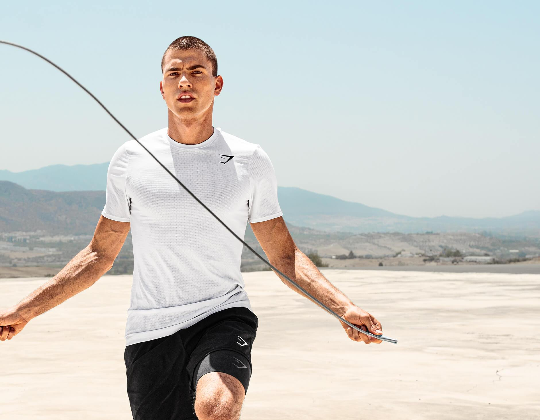 A male model skipping with a rope in desert whilst wearing the Arrival collection.