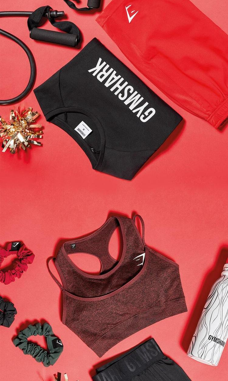 Christmas Flatlay of womens cherry brown Vital Rise Sports bra, black Training shorts, mens red Sport Shorts, black Apollo Tee and accessories
