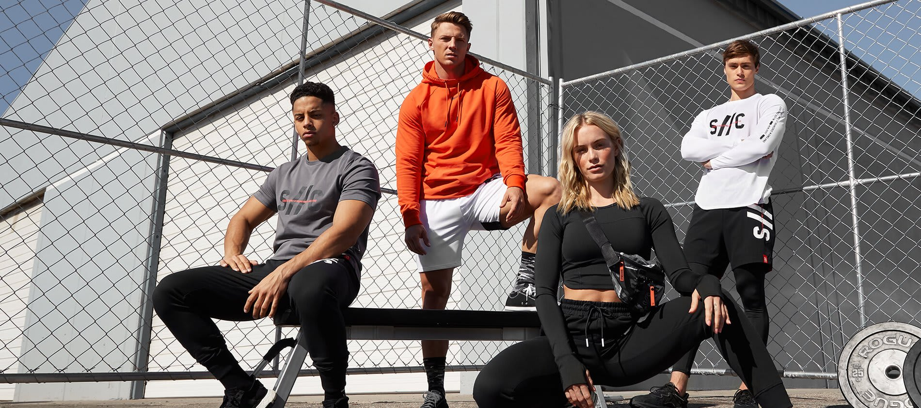 4 Gymshark athletes including Steve Cook posing together in front of a wire fence wearing the Steve Cook Collection.
