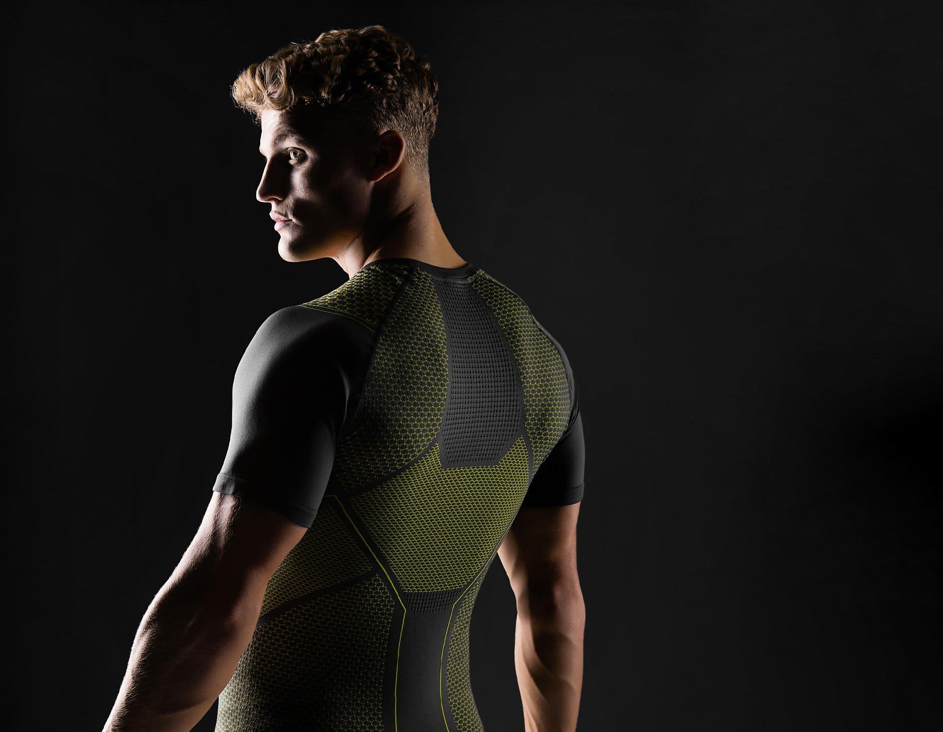 Mannelijk model met een zwarte achtergrond, laat rug detail zien van het charcoal/lime Onyx T-shirt.