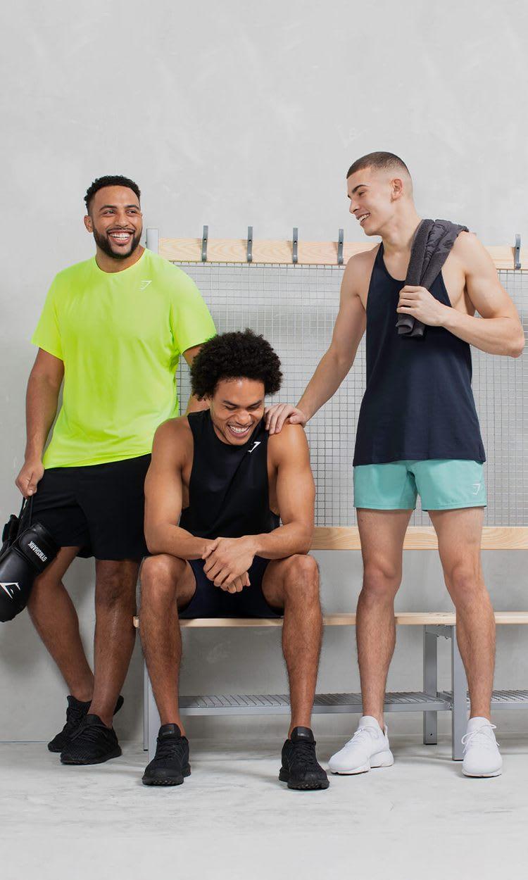 Drei männliche Models, die zusammen lachen, posieren in einem hellen Umkleideraum und tragen die Kollektion Gymshark Essentials.