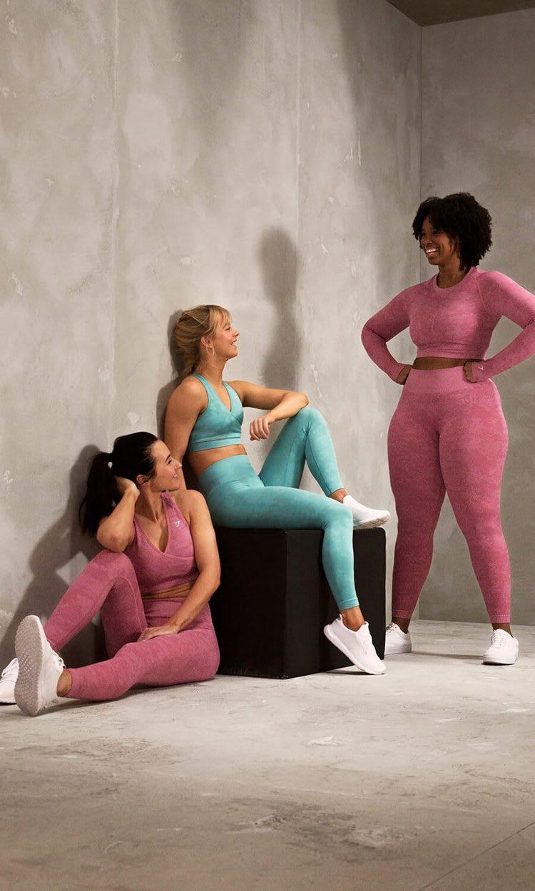 3 Gymshark Athleten lächeln sich an und tragen dabei die Camo Seamless Kollektion.