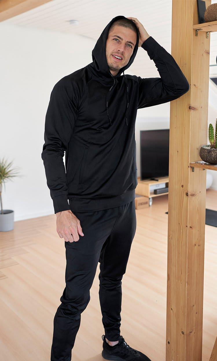 Ein Gymshark Athlet posiert in seinem Zuhause mit seinen Händen über dem Kopf und trägt die neue Reboot Kollektion.