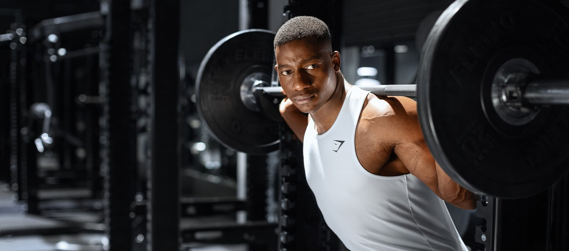 Der männliche Gymshark Athlet Lubomba bereitet sich darauf vor, eine Gewichtsstange vom Kniebeugen Reck zu heben in einem dunklen Fitnesstudio. Er trägt die Gymshark Critical Kollektion.