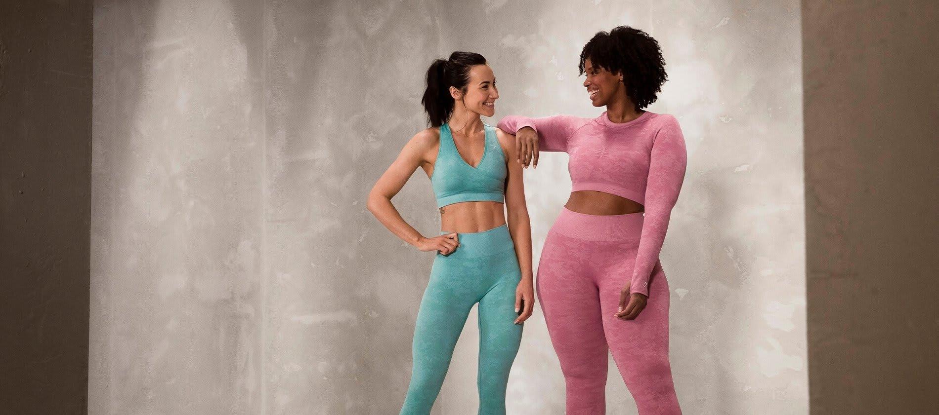 2 Gymshark Athleten lächeln sich an und tragen dabei die Camo Seamless Kollektion.