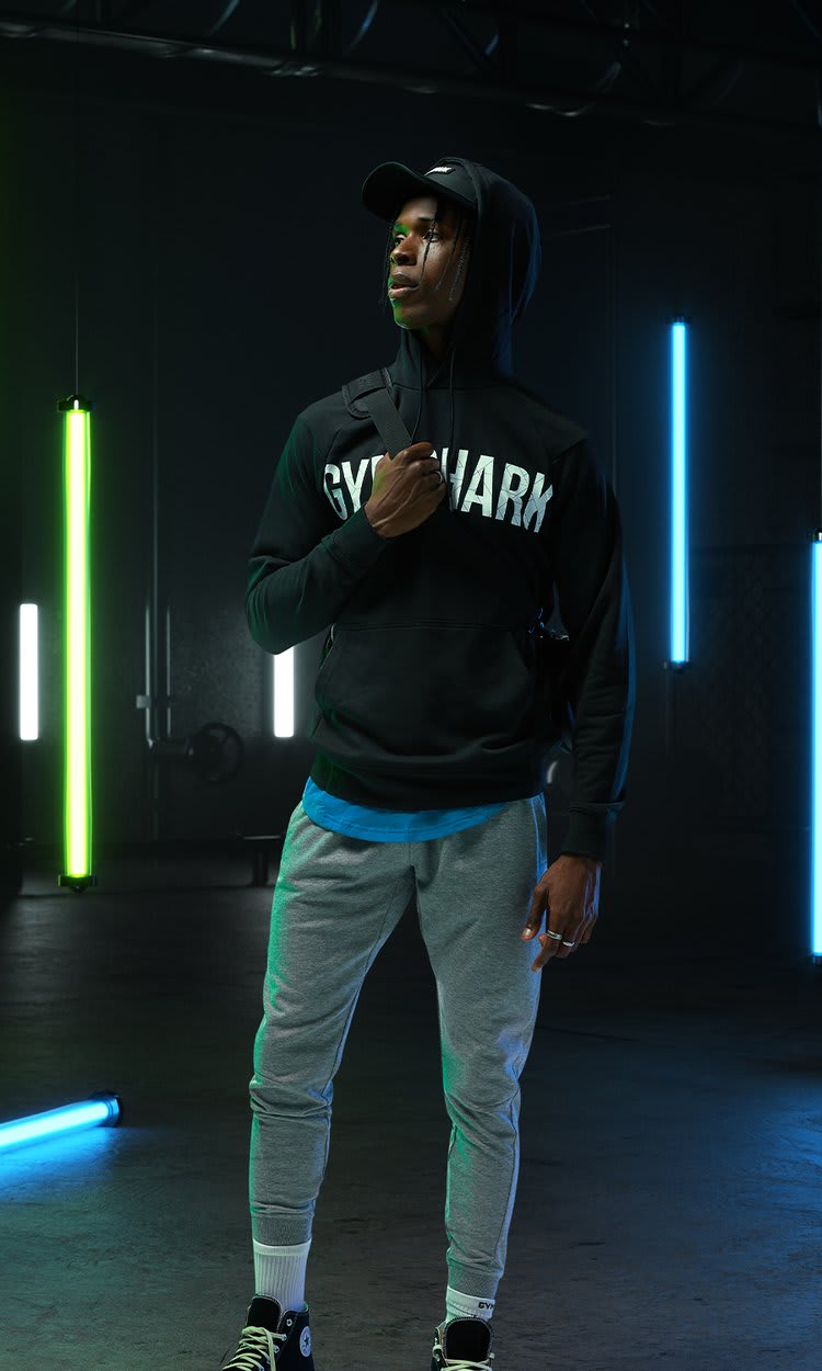 Male model posing in the new Bold collection in a dark room with vertical neon blue and green lights behind him.