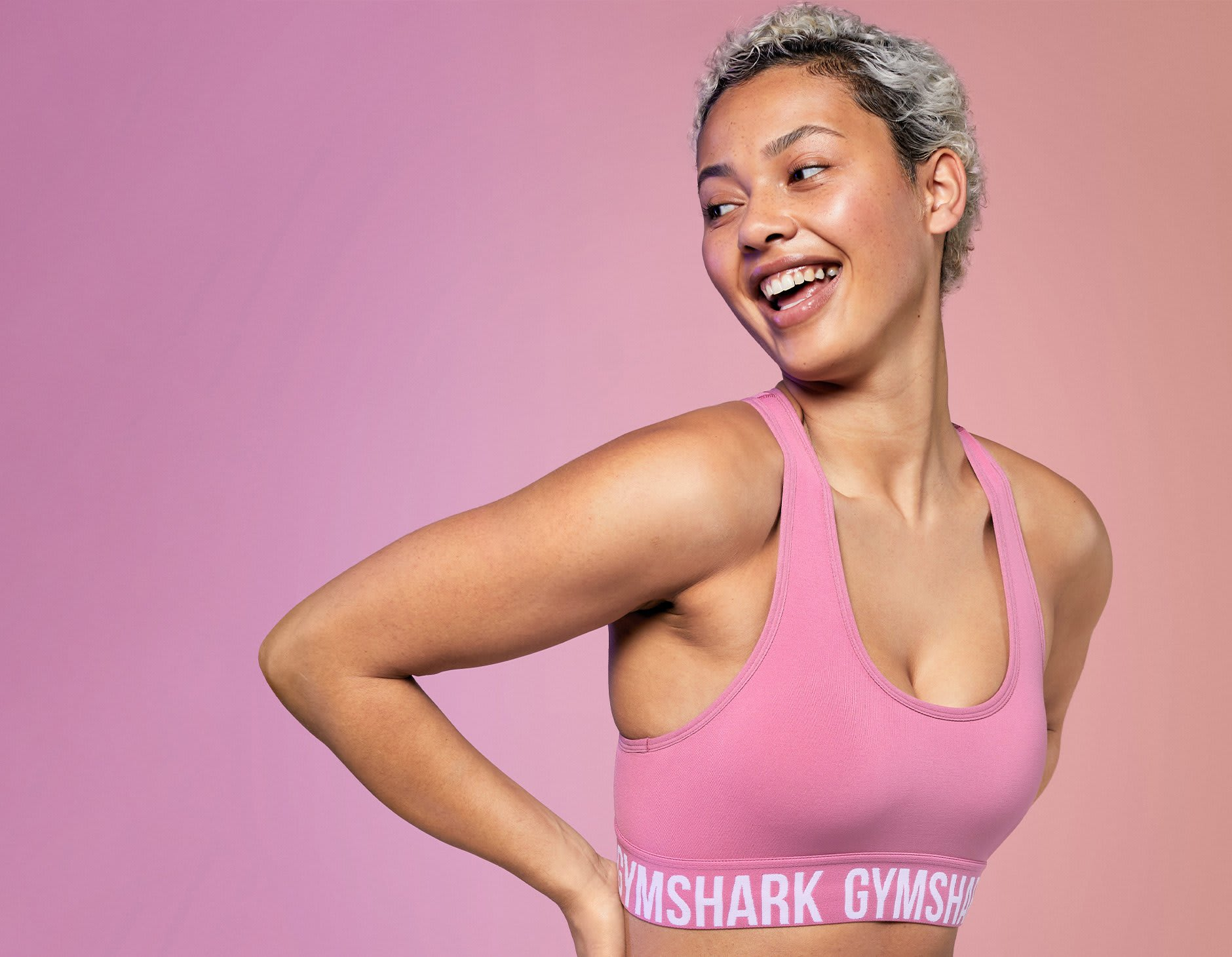 Female smiling while wearing the Fit Sports Bra in Pink infront of a pink background.