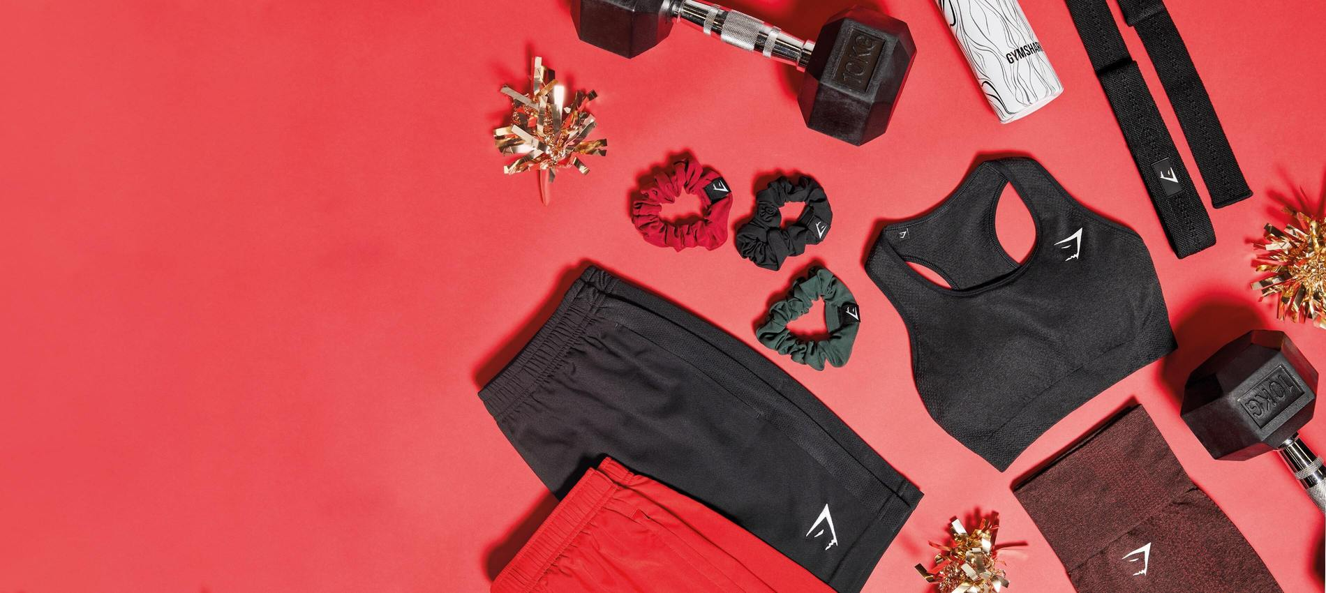 Christmas flatlay of womens Black Vital Seamless Sports bra and cherry brown Leggings, black and red mens Sport Shorts and accessories.