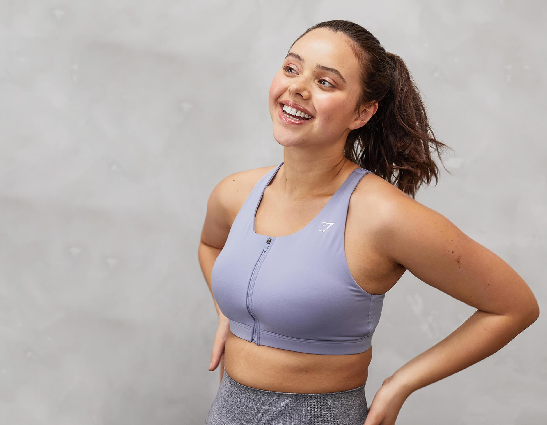 A model wearing a purple Gymshark sports bra posing very happily in front of a grey concrete wall.