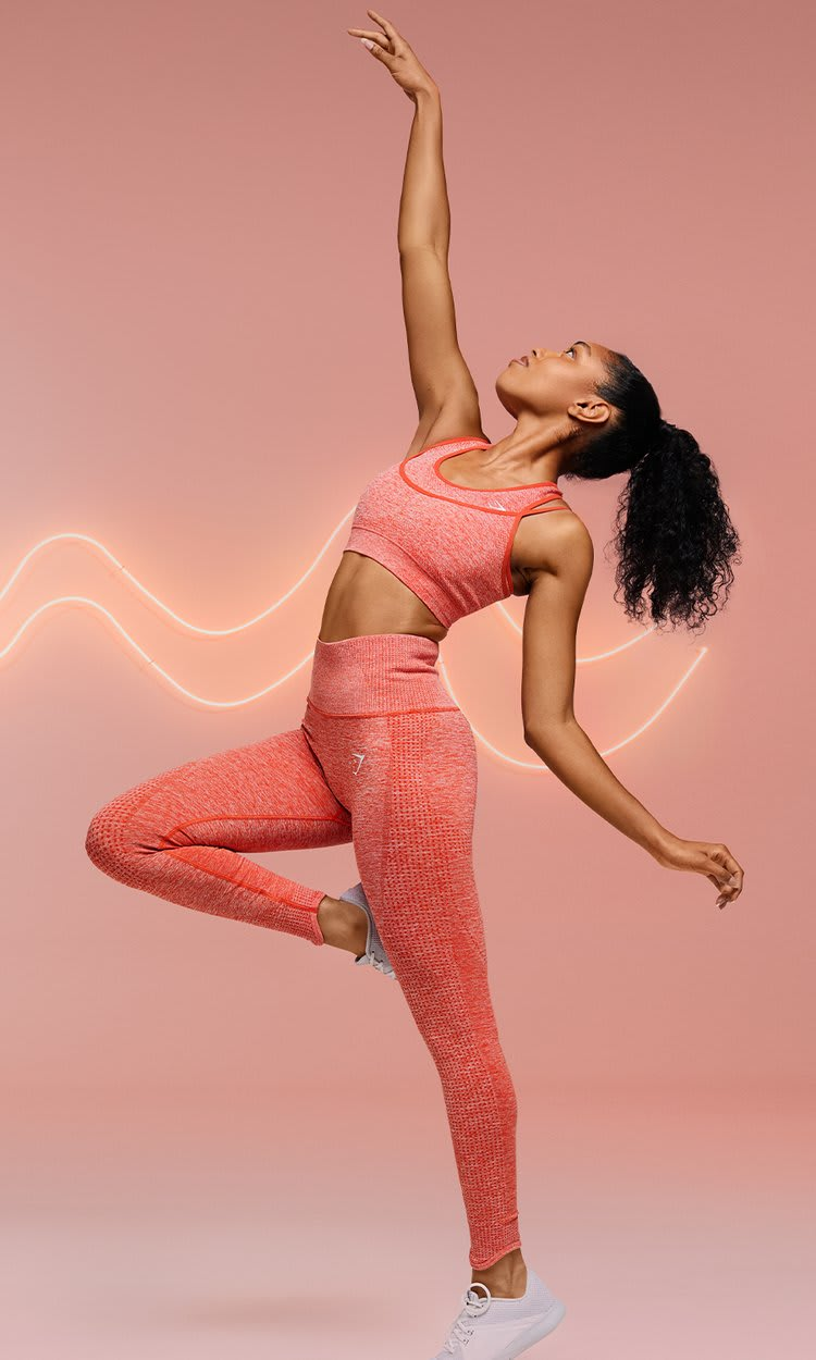 Models posing in the new Vital Rise leggings and sports bra in heat red marl against a pink background with neon lights.