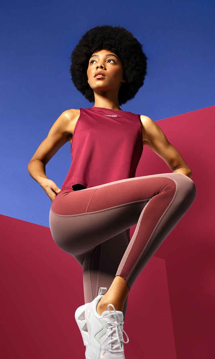 Model Posing in the Euphoria burgundy tank and taupe tone leggings against a red and blue background.
