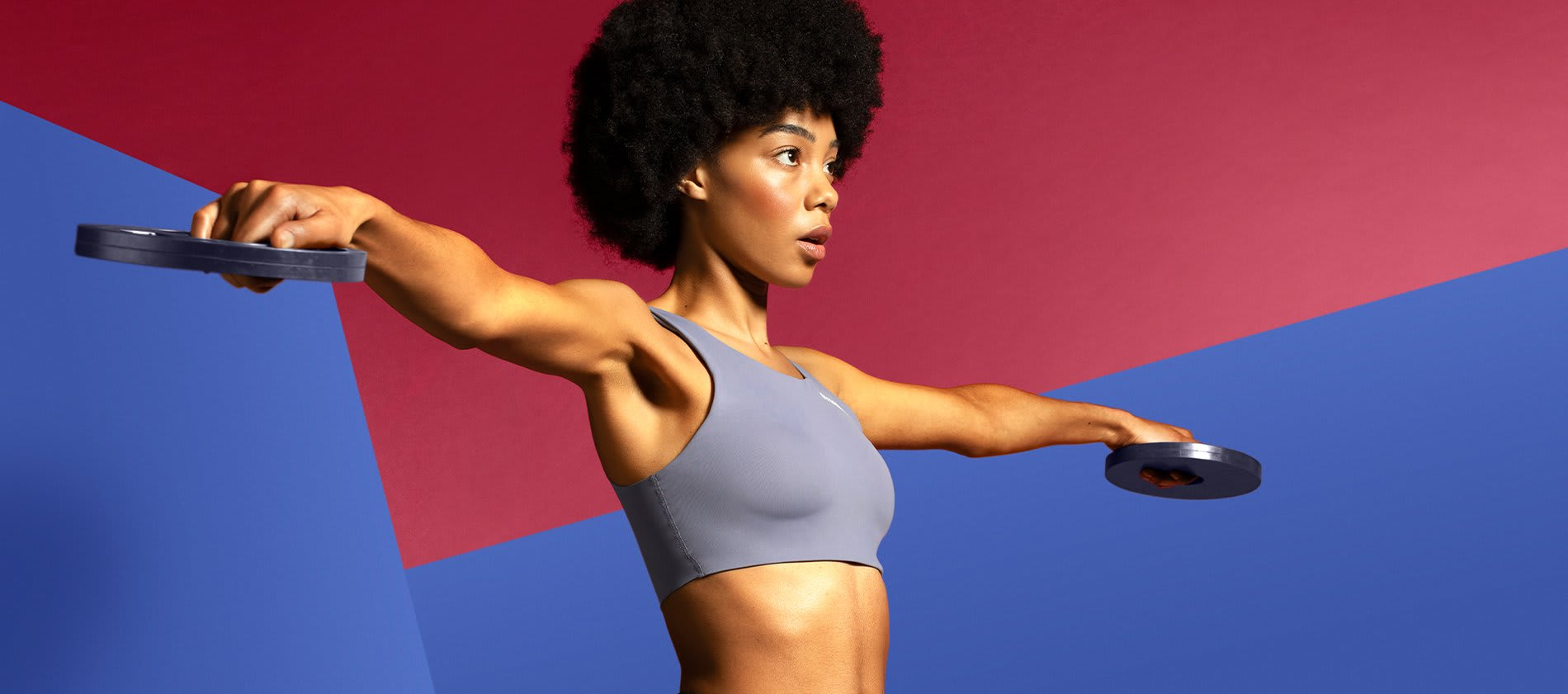 Model wearing blue Euphoria sports bra stretching her arms out to the side holding circular weights against a blue and red background.