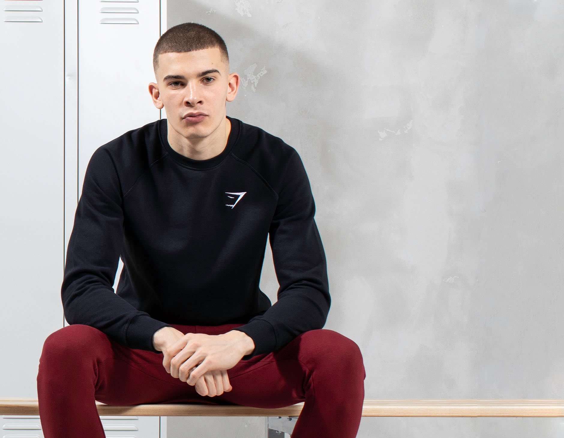 A male model sitting down resting his arms on his legs wearing the essentials collection.