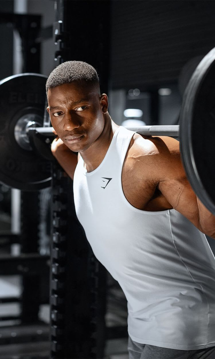 Male athlete Lubomba preparing to lift in a darkly lit gym wearing the must have Critical collection.
