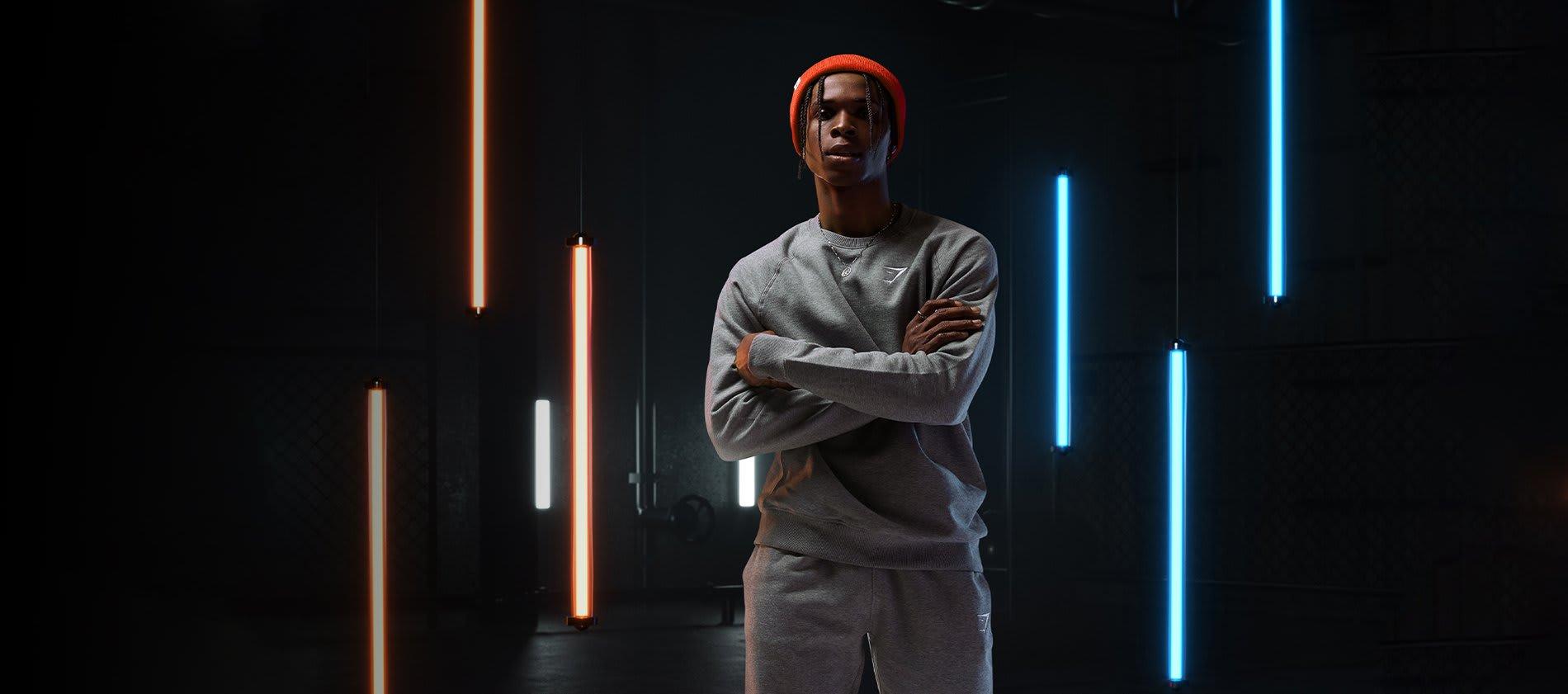 Mann trägt Crest Sweater und Jogger in Charcoal Marl in einem dunklen Raum mit orangen und blauen Neonröhren, die hinter ihm hängen.
