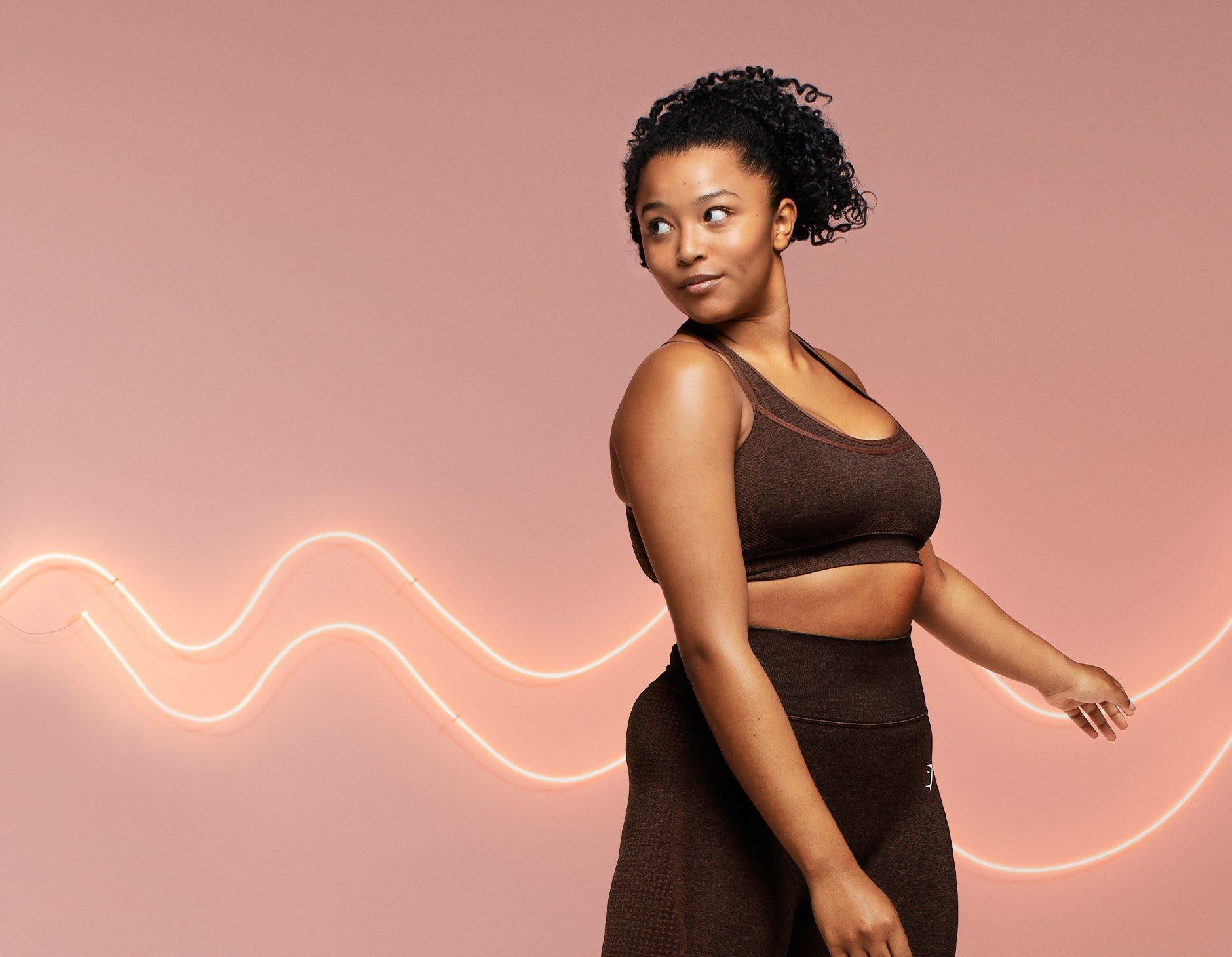 Weibliches Model posiert in dem neuen Vital Rise Sport-BH und der Leggings in Cherry Brown Marl vor einem pinken Hintergrund mit Neonlichtern.