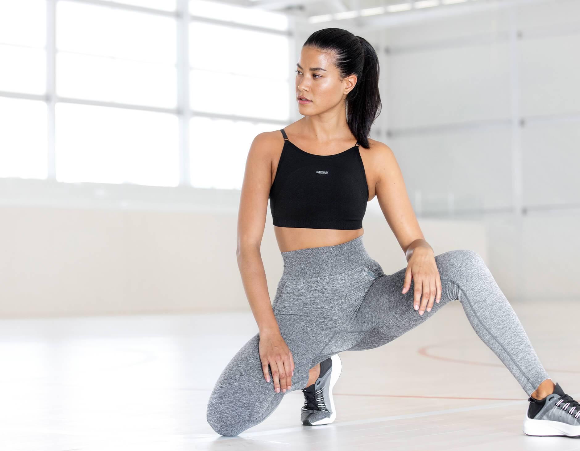 Ein weibliches Model, das sich in der Gymshark Flex-Kollektion in einer hell erleuchteten Szene hinhockt.