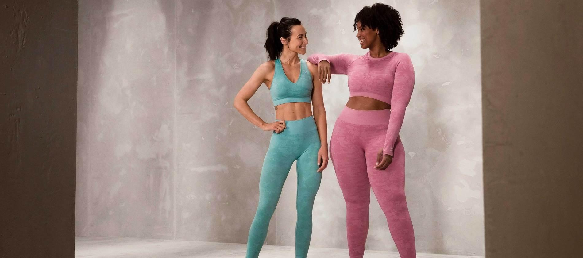 Zwei weibliche Gymshark Athletinnen lächeln und posieren zusammen vor einer Betonwand und tragen die Adapt Camo Kollektion.
