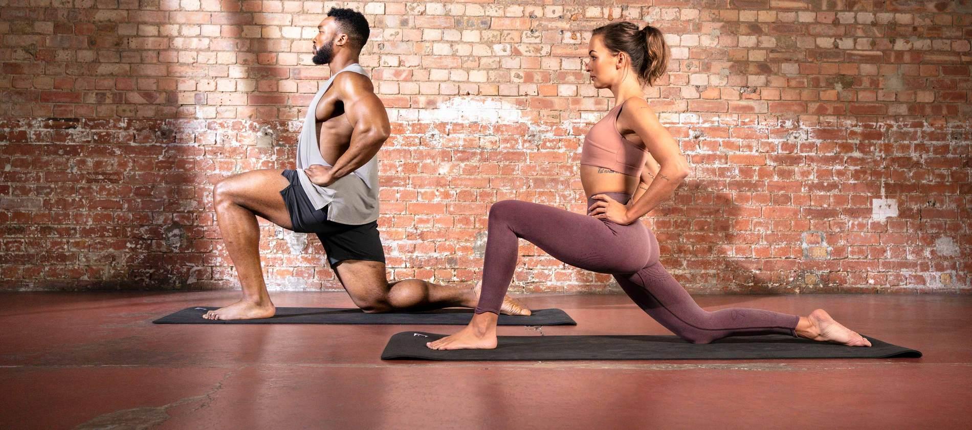 Ein weibliches und ein männliches Model dehnen sich auf Yogamatten in einem Yogastudio und tragen dabei die Gymshark Studio Kollektion.