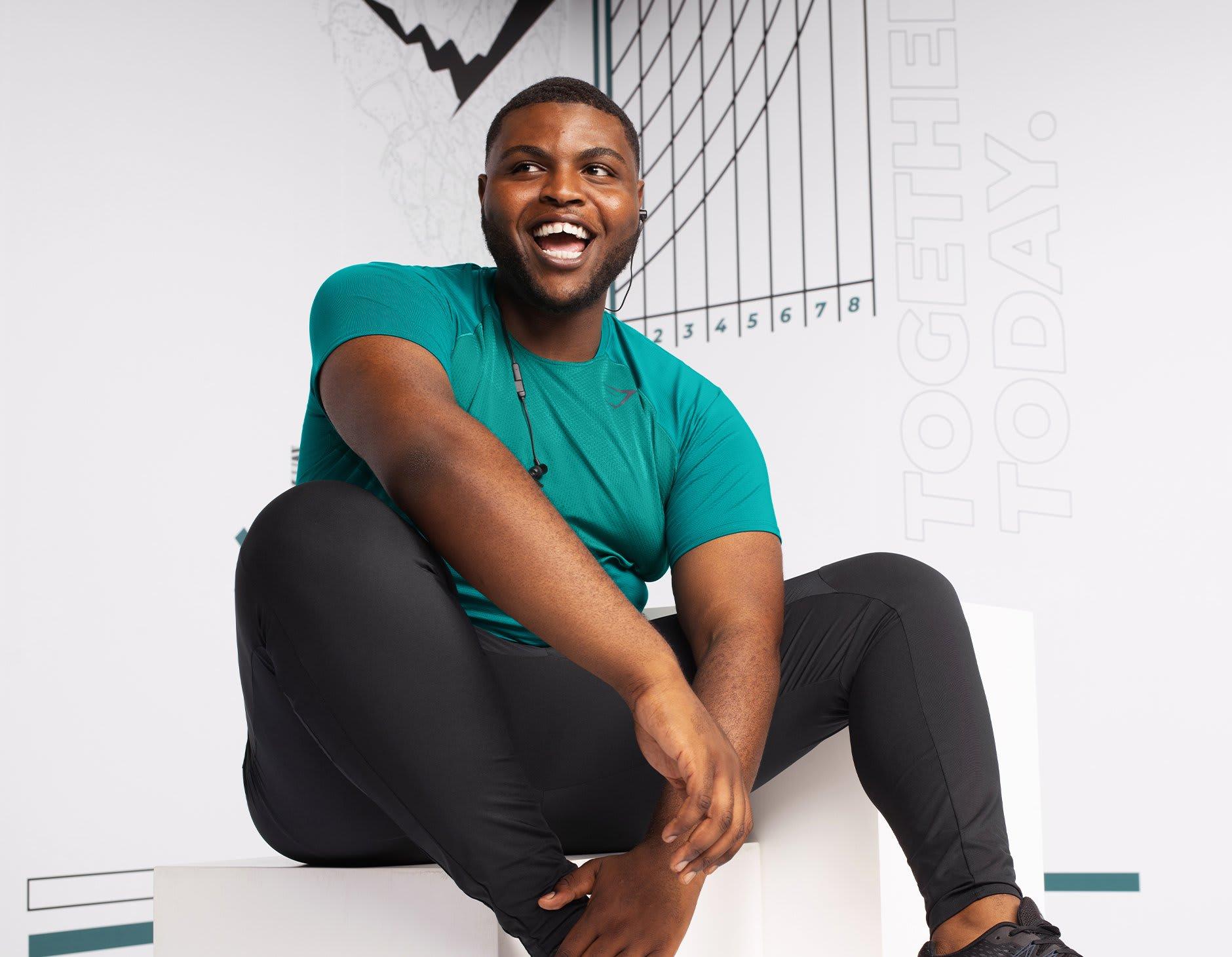 Männliches Model lacht sitzend und trägt dabei die Speed Kollektion vor einem weißen Hintergrund mit blauen, schwarzen und grauen Grafiken.