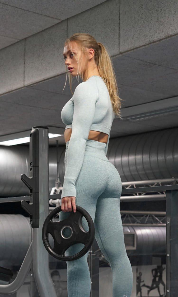 Gymshark Athletin Guusje posiert mit Gewichten in einem leicht beleuchteten Gym und trägt eine Vital Rise Leggings und ein Vital Seamless Crop-Top.