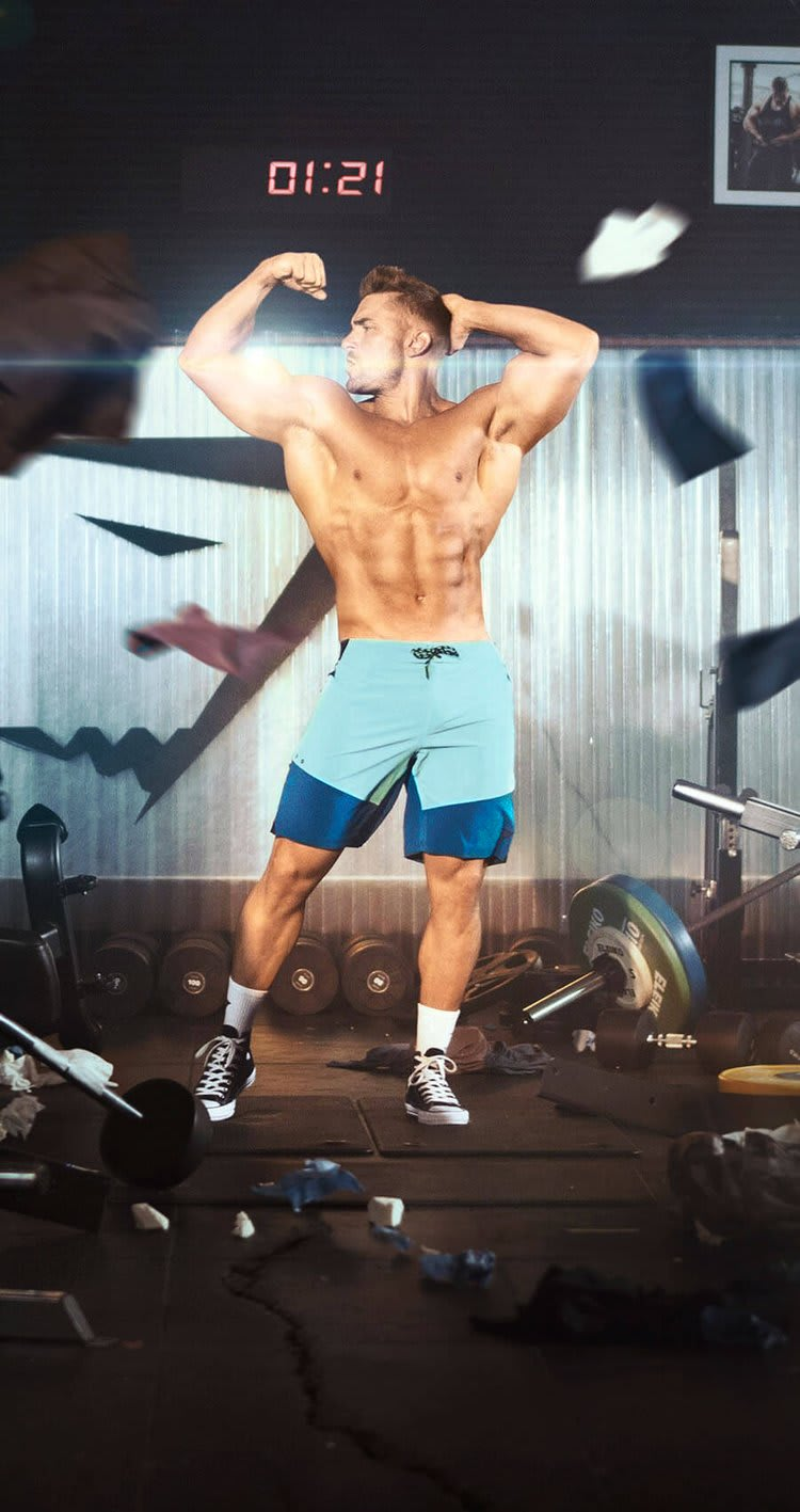 Ryan Terry posing in Blue Swim Shorts surrounded by weights in the gym.