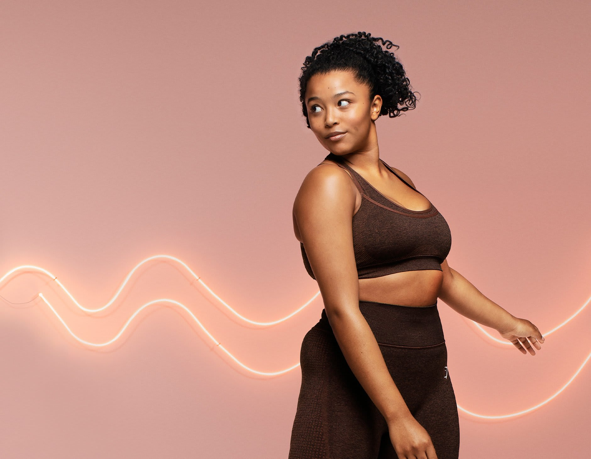 Female model posing in the new Vital Rise Sports bra and leggings in cherry brown marl against a pink background with neon lights.